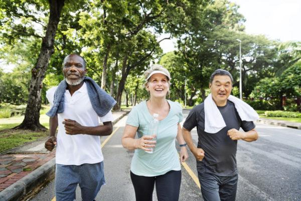 Group of senior friends jogging together in a park